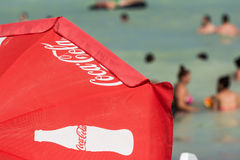 在海滩的可口可乐伞 免版税库存图片