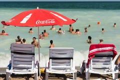 在海滩的可口可乐伞 免版税库存照片