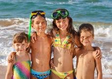 在海滩的四个孩子 免版税图库摄影