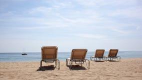 在海滩的四张海滩睡椅 库存图片