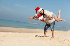 在海滩的圣诞节夫妇 免版税库存图片