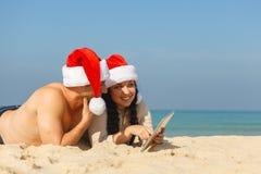 在海滩的圣诞节夫妇 免版税库存照片