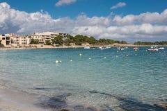 在海滩的场面与小船和房子 免版税库存照片
