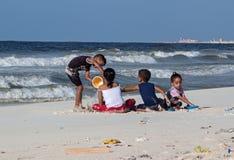 在海滩的埃及儿童游戏2014年10月09日的地中海在亚历山大,埃及 Postrevolutionary危机r 库存照片