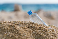 在海滩的塑料瓶 免版税库存照片