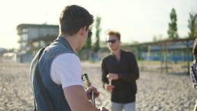 在海滩的夏天党 喝鸡尾酒的年轻朋友,跳舞在cirkle,弹吉他,唱歌歌曲和 股票录像