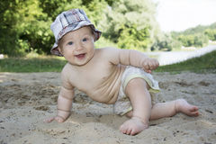 在海滩的夏令时在河附近坐滑稽的小男孩和 库存照片
