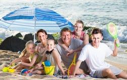 在海滩的大愉快的家庭坐周末 免版税库存图片