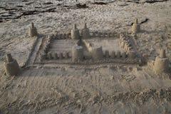 在海滩的大,并且简单的沙子城堡与在ba的海草 免版税库存照片