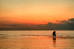 在海滩的夫妇在日落 库存图片