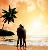 在海滩的夫妇在日落 免版税库存图片