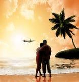在海滩的夫妇在日落 免版税库存照片
