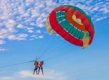 在海滩的夫妇帆伞运动 图库摄影