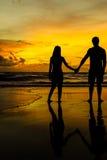 在海滩的夫妇日落的 库存照片