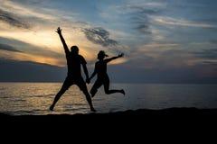 在海滩的夫妇silhuette在日落期间 免版税图库摄影