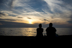 在海滩的夫妇silhuette在日落期间 库存图片