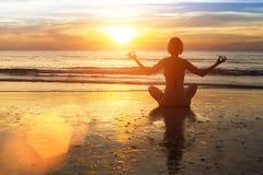 在海滩的女子实践的瑜伽在惊人的日落的焕发 免版税库存照片
