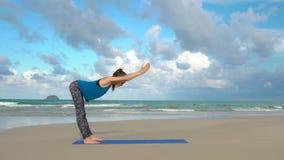 在海滩的女子实践的瑜伽在日落 健康生活方式 锻炼平静和和谐 免版税库存照片