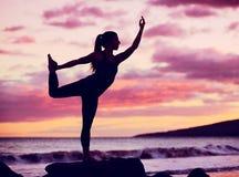 在海滩的女子实践的瑜伽在日落 免版税库存图片