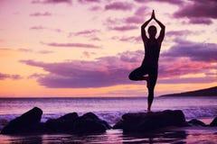 在海滩的女子实践的瑜伽在日落 免版税库存照片