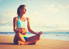 在海滩的女子实践的瑜伽在日落 免版税图库摄影