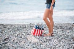 在海滩的女孩立场 美国旗子袋子 免版税库存图片