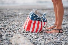 在海滩的女孩立场 美国旗子袋子 库存图片