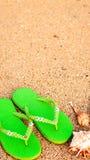 在海滩的妇女凉鞋在海岸线 免版税库存照片