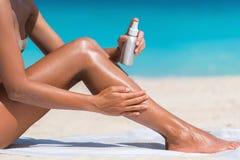 在海滩的妇女喷洒的遮光剂晒黑化妆水 免版税库存图片