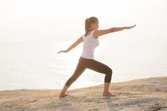 在海滩的妇女实践的战士瑜伽姿势 图库摄影