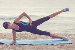 在海滩的妇女训练,锻炼 概念体育健康生活方式 免版税库存图片