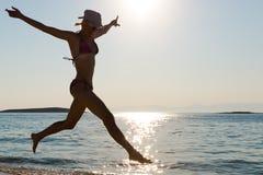 在海滨的妇女跳跃的背后照明 免版税库存图片