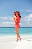 在海滩的妇女饮用的鸡尾酒 免版税图库摄影