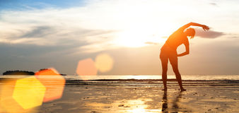 在海滩的妇女锻炼在日落 体育运动 免版税库存图片