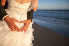 在海滩的婚礼曲拱附近结合微笑和拥抱 在海或海洋的蜜月 免版税库存图片
