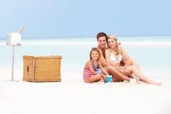 在海滩的家庭与豪华香宾野餐 免版税库存照片