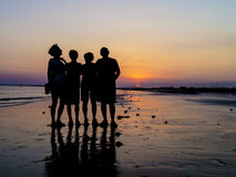 在海滩的家庭在日落 免版税库存照片