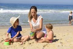 在海滩的家庭度假:母亲和孩子 免版税图库摄影