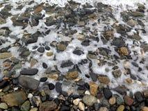 在海滩的小卵石与波浪 免版税库存照片