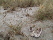 在海滩的小女孩的失去的鞋子 免版税库存照片