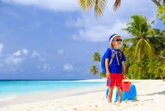 在海滩的小男孩旅行带着手提箱 库存图片