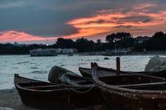 在海滩的小船在日落下 库存照片