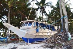 在海滩的小船在棕榈树之间的缆绳 图库摄影