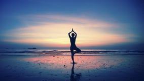 在海滩的少妇实践的瑜伽剪影在惊人的日落 凝思 图库摄影