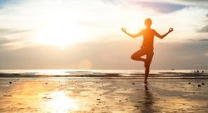 在海滩的少妇实践的瑜伽在日落 凝思 免版税库存照片