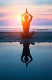 在海滩的少妇实践的瑜伽在日落 库存照片