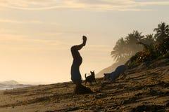 在海滩的少妇实践的瑜伽 免版税库存图片