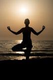在海滩的少妇实践的瑜伽 图库摄影