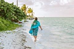 在海滩的少妇散步沿海洋 免版税图库摄影