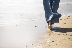 在海滩的少妇步行 免版税库存照片